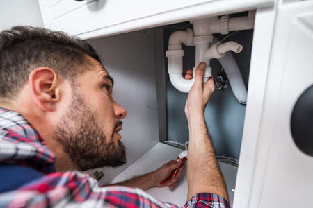 Male Plumber In Overall Fixing Sink Pipe Standard-Bild
