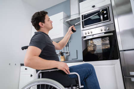 Disabled Man Using Grabber Tool To Control Microwave In Kitchen Stock Photo