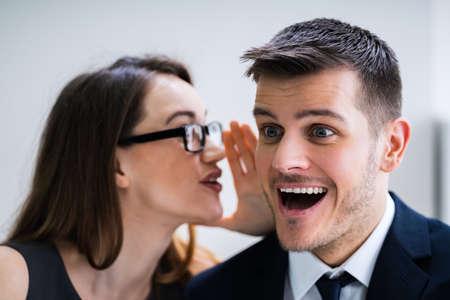 Porträt einer glücklichen Frau, die einem gutaussehenden Mann ein Geheimnis oder interessanten Klatsch ins Ohr flüstert Standard-Bild