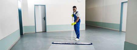 Man With Mop And Wet Floor Sign Stock Photo