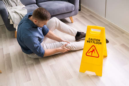 Man Falling On Wet Floor In Front Of Caution Sign At Home