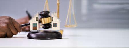 Close-up Of A Judge Striking Gavel Between Split House Over Desk