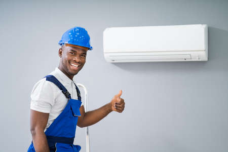 Smiling Male Electrician Gesturing Thumbs Up Near Air Conditioner Stockfoto