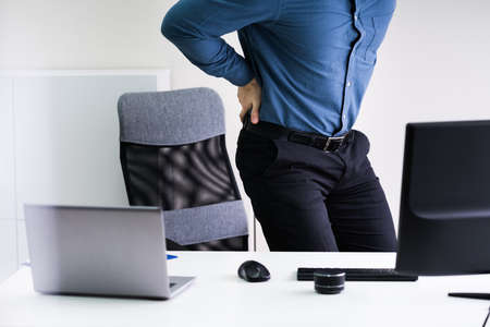 Businessman With Lower Back Ache Standing Near Office Desk