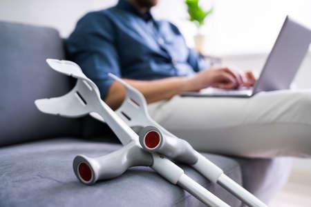Man With Leg Injury Sitting On Sofa Using Laptop