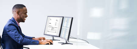Side View Of A Businessman Checking Invoice On Computer At Workplace Stock Photo