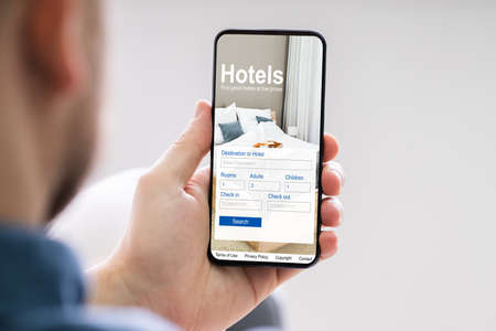 Close-up Of A Person Holding A Smart Phone Using Online Low Prices Hotels Application Imagens