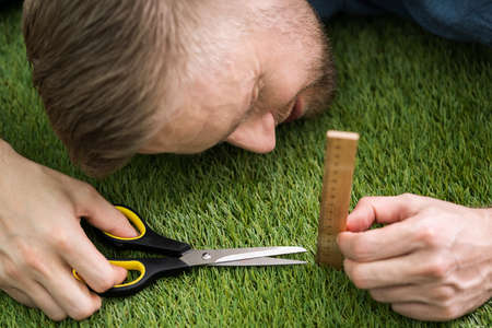 Close-up Of A Man Cutting Green Grass Measured With Ruler Фото со стока