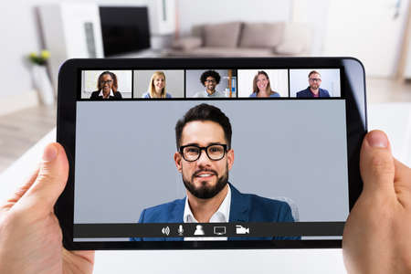 Man Working From Home Online Group Videoconference On Tablet Stock Photo