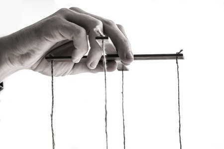 Close-up Of A Person's Hand Manipulating Marionette With String On Gray Background Archivio Fotografico