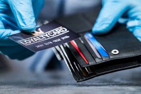 Consumer Taking Loyalty Card From Wallet In Gloves To Protect From Coronavirus
