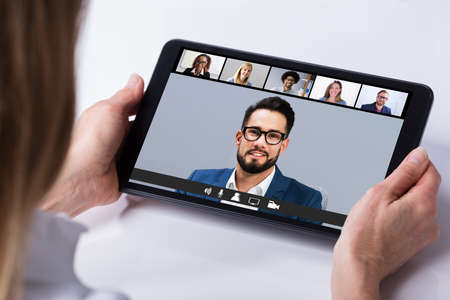 Woman Working From Home Having Group Videoconference On Tablet