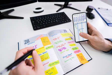 Close-up Of A Businessman Holding Cellphone Writing Schedule In The Diary With Pen