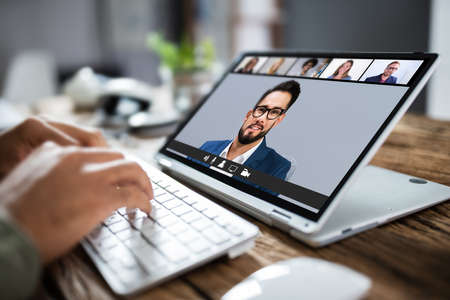 Man Having Online Group Videoconference On Laptop