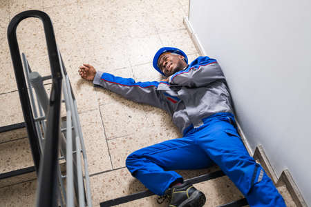 Injured Handyman Lying On Floor After Falling From Staircase