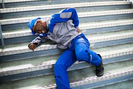 Worker Man Lying On Staircase After Slip And Fall Accident Stockfoto