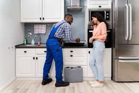 Woman Looking At Serviceman In Uniform Fixing Induction Stove In The Kitchen Zdjęcie Seryjne