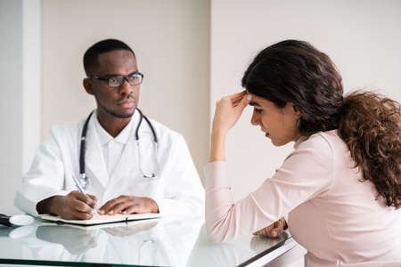Doctor Discussing With Female Patient In Clinic