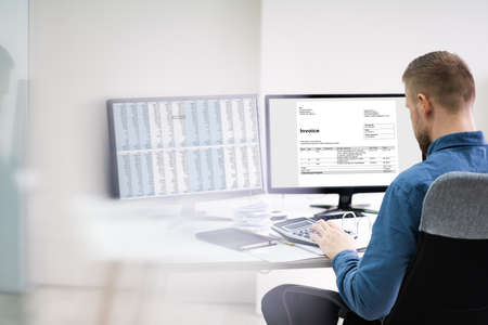 Close-up Of A Businessman Looking At Invoice On Computer At Workplace