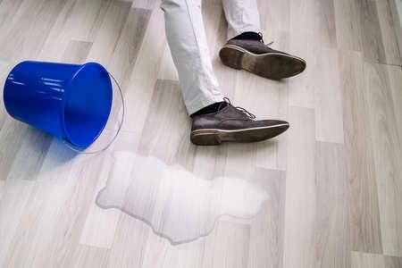 Hombre cayendo sobre el suelo mojado delante de un balde de agua derramada en casa