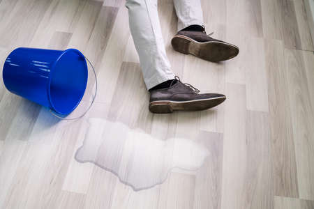Mann fällt auf nassen Boden vor verschüttetem Wassereimer zu Hause