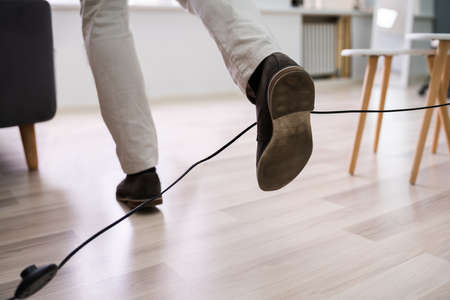 Close-up Of A Man Legs Stumbling With An Electrical Cord At Home Banque d'images