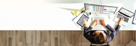 Multitasking Woman Working On Computer In Office