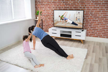 Fit Family Doing Online Fitness Workout Near Television