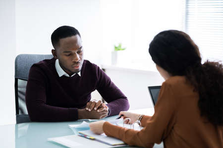Young Financial Advisor Discussing Invoice With Her Client At Workplace Standard-Bild