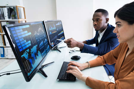 Side View Of Male And Female Stock Market Broker Analyzing Graphs On Laptop At Workplace