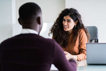 Female Manager Interviewing A Young Male Applicant In Office Stockfoto