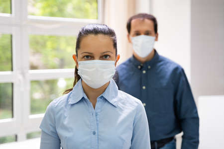 Two People Standing In Line Wearing Face Masks