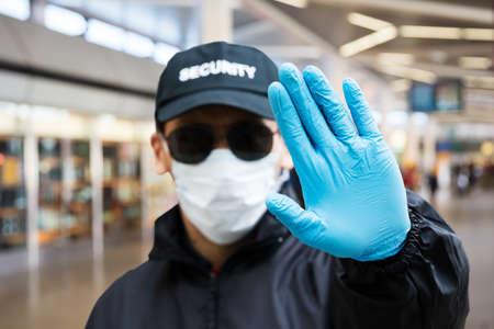Guardia de seguridad de pie en la mascarilla en la terminal del aeropuerto