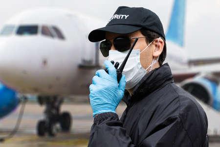 Agent de sécurité parlant sur talkie-walkie près de l'avion Banque d'images