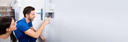 Alarm System Security Installation At Home. Technician Installing Near Door Stock Photo