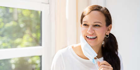 Woman Removing Face Mask To Breath Freely