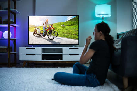 Woman Watching TV On Couch Or Sofa. Watch Television