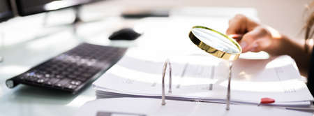 Wirtschaftsprüfer untersucht Unternehmensbetrug mit Lupe