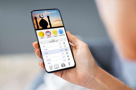 Woman Using Muslim Prayer App On Mobile Phone Standard-Bild