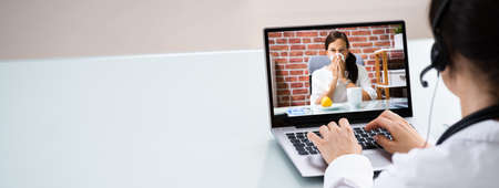 Doctor Talking To Patient Through Video Chat On Laptop At Desk