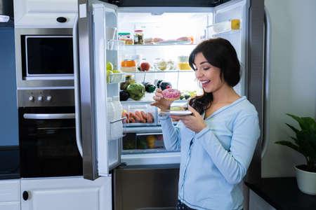 Woman Eating Unhealthy Food At Night Near Open Fridge