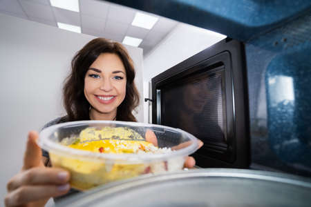 Young Woman Heating Fried Food In Microwave Oven Standard-Bild