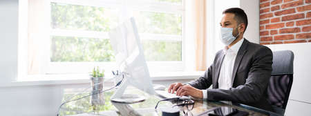 Man Employee In Office Wearing Face Mask Working On Computer