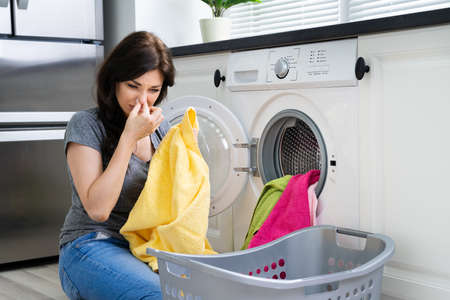 Young Woman Looking At Smelly Clothes Out Of Washing Machine In Kitchen Standard-Bild