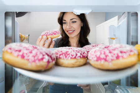 Happy Young Woman Taking Donut From Refrigerator Or Freezer Standard-Bild