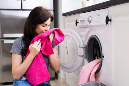 Woman Smelling Clothes At Home Doing Laundry