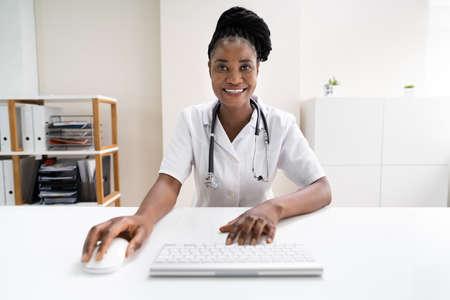 Happy African Woman With Stethoscope In Hospital Foto de archivo