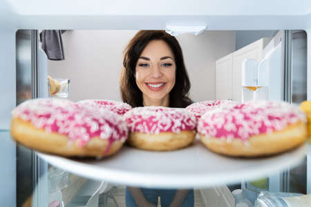 Happy Young Woman Looking At Donut From Refrigerator Or Freezer
