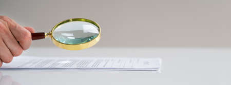 Fraud Auditor Using Magnify Glass On Business Document Paperwork