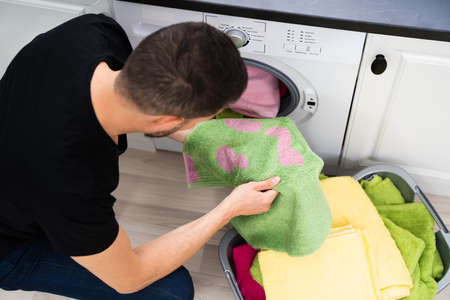 Man Doing Laundry. Stains On Clothes After Washing Machine